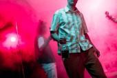 částečný pohled na člověka s lahví alkoholu během Rave v nočním klubu