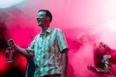 šťastný muž s láhví alkoholu při Rave v nočním klubu