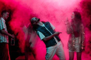 men and girls dancing in nightclub with pink smoke