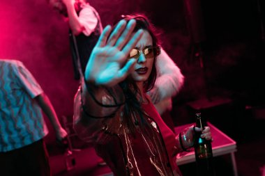 girl Gesturing with hand and holding bottle of alcohol during rave in nightclub