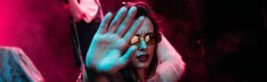 panoramic shot of girl in sunglasses showing hand at camera in nightclub during rave party