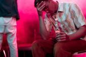 nemocný muž s bolestí hlavy a s lahví vody v nočním klubu