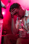sick man with headache sitting with bottle of water in nightclub