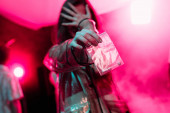 girl holding plastic zipper bag with drugs in nightclub and covering face