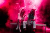 glücklicher Mann und junge Frau sitzen zusammen bei Rave-Party in Nachtclub