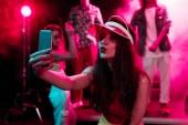Mädchen pöst Lippen und selfie auf dem Smartphone während Rave-Party in Nachtclub