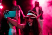 boldog lány vesz selfie a smartphone alatt rave fél nightclub