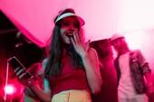 überrascht Mädchen mit Smartphone bedeckt Mund während Rave-Party in Nachtclub