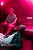 smiling man lying on floor in nightclub during rave party with pink smoke