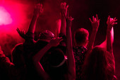 back view of people with raised hands during rave party in nightclub with pink lighting