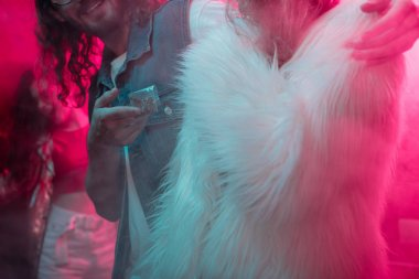 cropped view of man giving weed in plastic zipper bag to girl in nightclub
