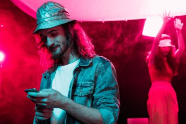 man using smartphone during rave party in nightclub