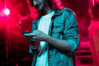 Cropped view of man using smartphone during rave party in nightclub