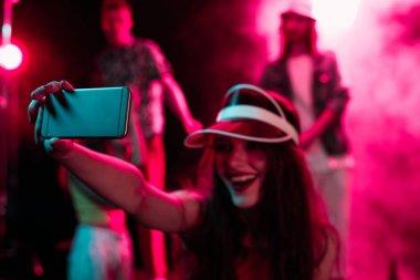 happy girl taking selfie on smartphone during rave party in nightclub