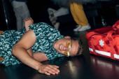 muž ležící na podlaze nedaleko první pomoci taška v nočním klubu
