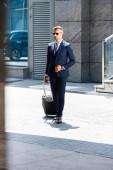 pohledný muž v obleku a brýle držící kufr a pohled