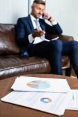 selektivní zaměření papírů na stůl a muž hovoření o smartphone na pozadí