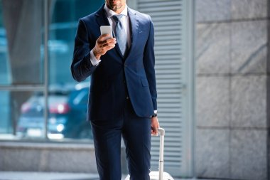 Cropped view of man in suit using smartphone outside stock vector