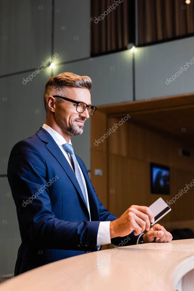 Handsome businessman in suit and glasses smiling and giving credit card stock vector