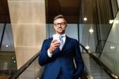 pohledný obchodník v obleku a brýle používající smartphone v hotelu