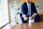 Ausgeschnittene Ansicht von Geschäftsmann im Prozess nimmt Tasse und hält Zeitung