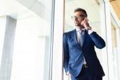 schöner Geschäftsmann in formeller Kleidung und Brille, der auf dem Smartphone spricht