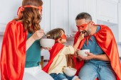 boldog család a jelmezek a szuperhősök eszik reggelit, míg fia etetés apja pelyhek