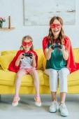 Kyiv, Ukrajna-július 5, 2019: boldog anya és lánya jelmezek a szuperhősök játék közben ülve a kanapén otthon