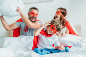 happy family in costumes of superheroes fighting with pillow in bed