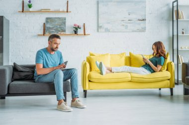 woman lying on yellow sofa with smartphone near husband sitting on couch and using smartphone