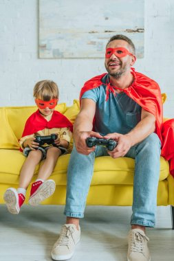 KYIV, UKRAINE - JULY 5, 2019: Cheerful father and son in costumes of superheroes sitting on sofa and playing video game stock vector