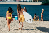 back view of young man holding surfboard while walking near girl in swimsuit