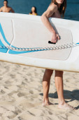 partial view of young sportsman holding surfing board on beach