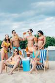 fiatal, multikulturális barátok sört, miközben a strandon