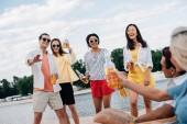 veselí, mladí multikulturní přátelé s zábavou a popíjením piva na pláži