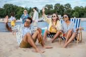 pohledný multikulturní muž, který mává rukama a baví se s přáteli na pláži