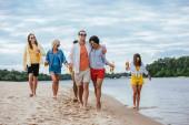 během chůze po břehu řeky spolu s multikulturistama se propléhají dvojice