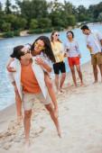 schöner junger Mann huckepack glückliche Freundin, während Spaß am Strand zusammen mit multikulturellen Freunden