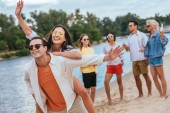 Veselý mladý muž, který se při chůzi na pláži s multikulturými přáteli oplájí šťastnou přítelkyní
