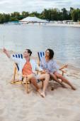 boldog Interracial pár ül a Utazókocsi társalgók és a gazdaság csillagszórók pihenő a strandon