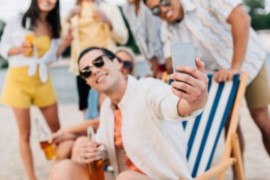 Selective focus of cheerful young man taking selfie with multicultural friends having fun on beach stock vector