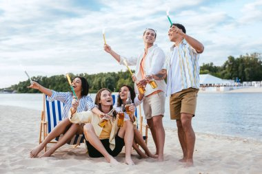 Happy multicultural friends having fun on beach while holding sparklers and bottles of beer stock vector