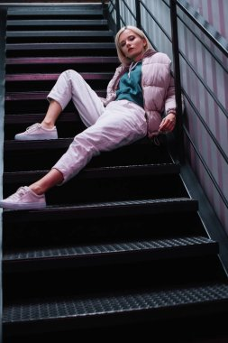 Blonde girl in down jacket and sneakers sitting on stairs and looking at camera stock vector