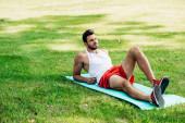 pohledný sportovec ležící na fitness, v parku