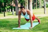 handsome man doing plank exercise on fitness mat