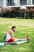vousatý sportovní muž sedící na fitness rohoži na trávníku