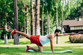 bearded athletic sportsman working out on fitness mat outside