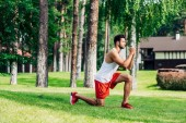 handsome athletic man training near trees in park