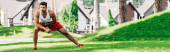 panoramic shot of handsome man warming up while exercising on lawn