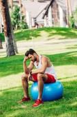 rozčilený sportovec sedící na modré fitness kouli v parku
